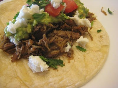 Slow Cooker Mexican Pulled Pork on a taco with queso fresco, cilantro, and guacamole