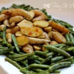 Roasted fingerling potatoes surrounded by green beans with tarragon cream dressing served on a platter