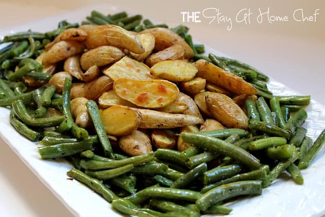 Potatoes and green beans on a white serving dish.