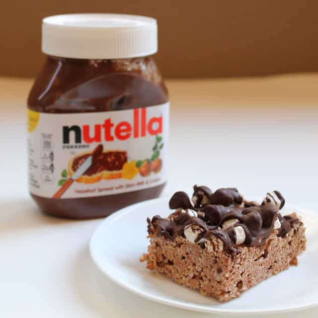 Slice of Nutella Krispies on a plate with jar of Nutella in the background