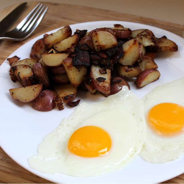 Potatoes, bacon, and eggs on a white plate.