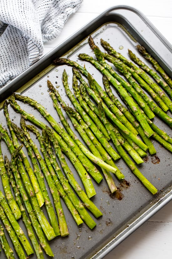 Oven roasted Asparagus lined up on a baking sheet