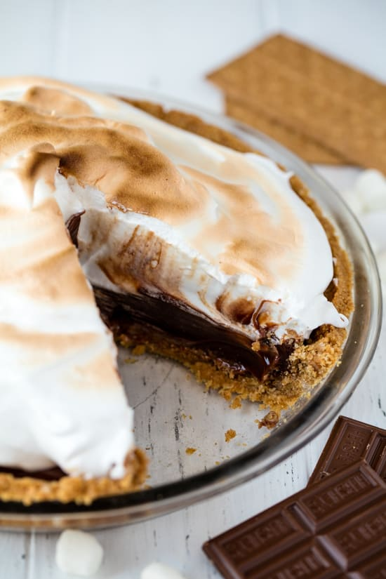 Homemade smores pie from scratch layered with graham cracker crust, hot fudge filling and topped with Italian meringue