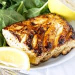 Grilled halibut with a salad and lemon wedges on a white plate with a fork nearby