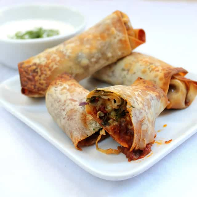 Baked Mexican Egg rolls on a white plate with Cilantro-Lime Crema