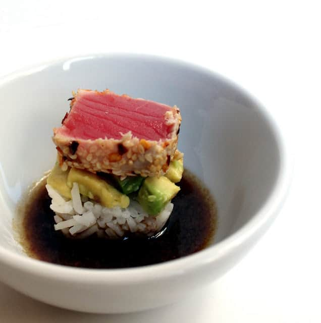 Ahi Avocado sushi in a bowl of soy sauce.