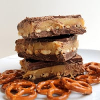 A stack of Chocolate Pretzel Caramel Bars surrounded by pretzels