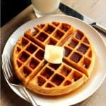 Greek Yogurt Waffle topped with syrup and a pad of butter on a white plate with a fork and butter knife.