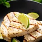 Grilled Swordfish fish on a black plate topped with a lime wedge.
