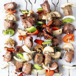 Seven Marinated Steak Kebabs on a countertop.