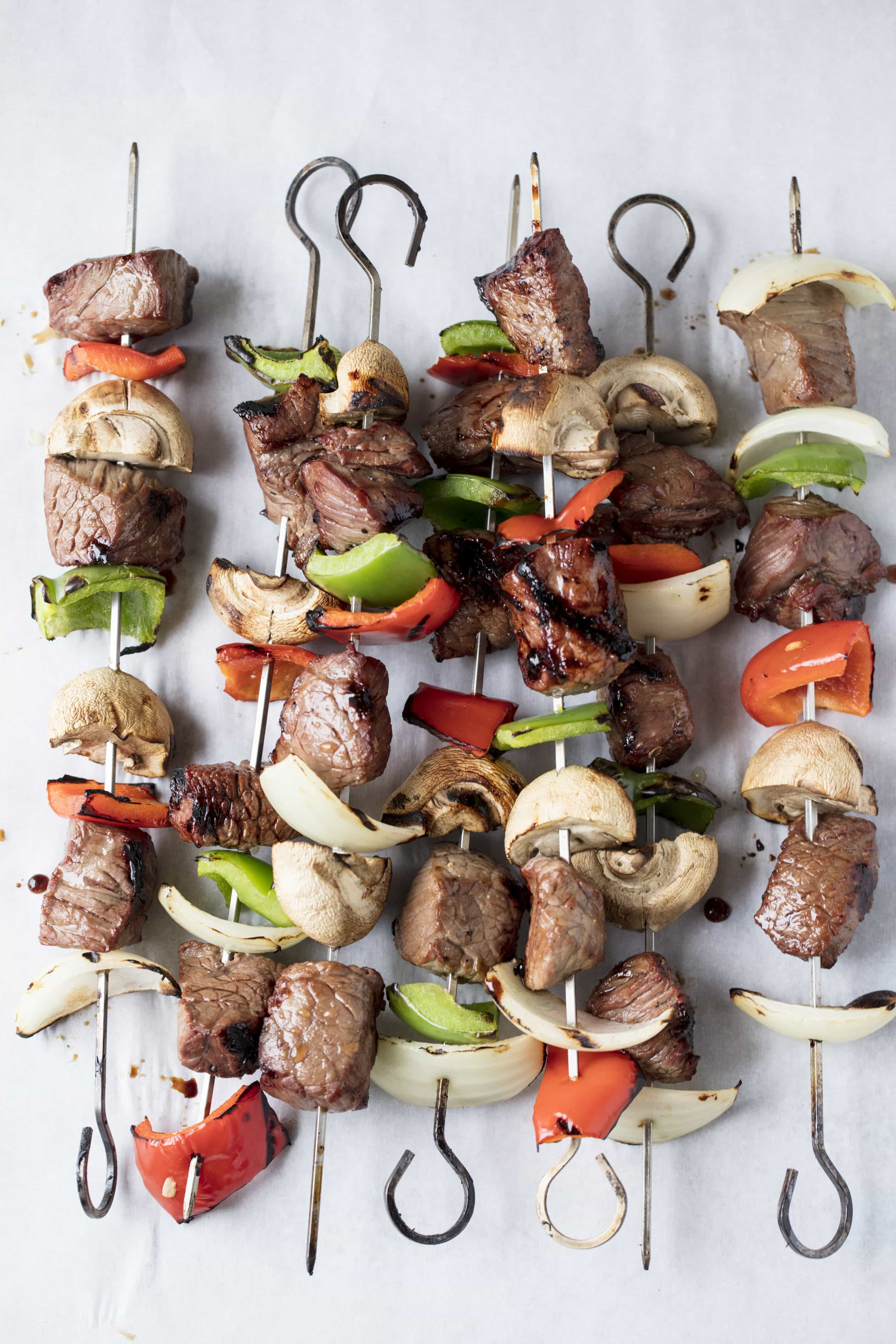 Chunks of beef, bell peppers, and mushrooms threaded onto 7 different skewers