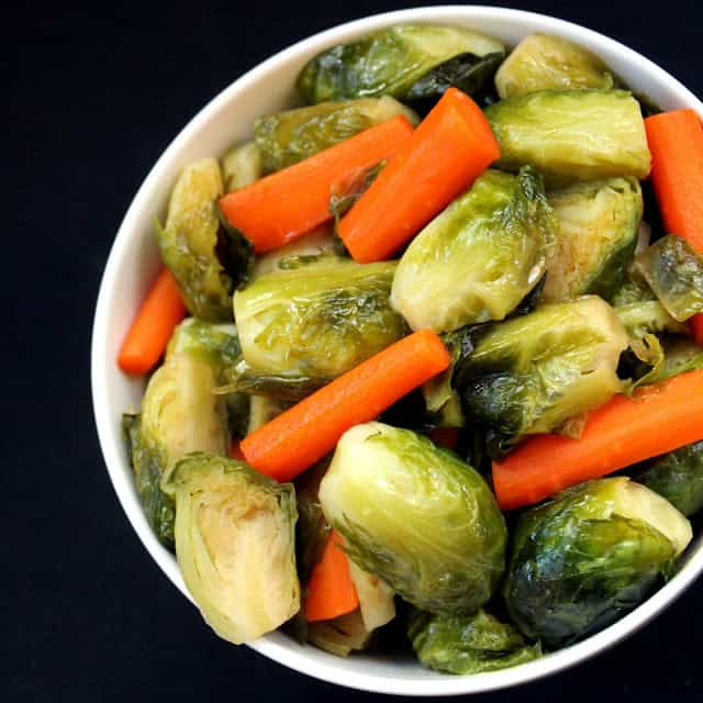 Maple Brussel Sprouts and carrots in a white bowl.