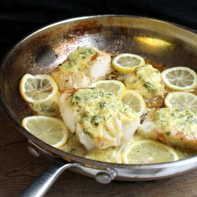 Cod Fish covered in a lemon sauce and surrounded by lemon slices in a skillet.