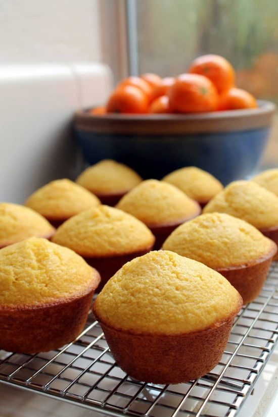 Cornbread muffins in a row, cooling on a cooling rack in front of a window