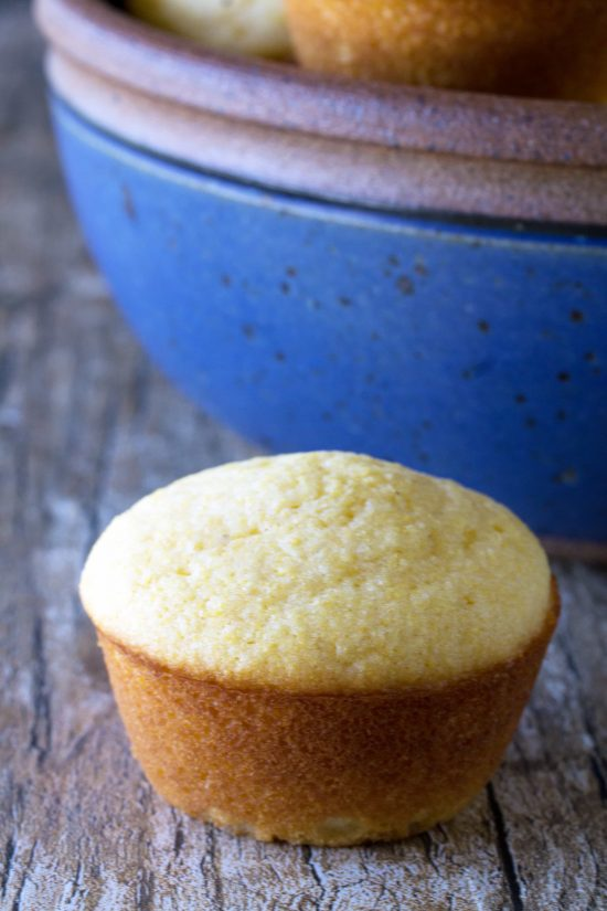 Buttermilk cornbread muffin on a wood surface in front of a blue bowl
