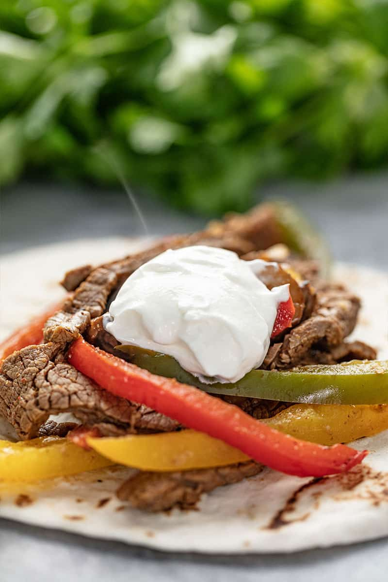 Steak Fajita topped with sour cream on a tortilla.