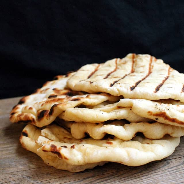 A stack of freshly grilled Homemade Naan Bread
