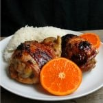 Orange Glazed Chicken Thighs served with coconut rice and slices of fresh oranges