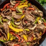 Bird's eye view of Steak Fajitas in a cast-iron skillet.