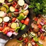 Fresh vegetables tossed with seasoning in a pan and grilled veggie kebabs on metal skewers on a cutting board