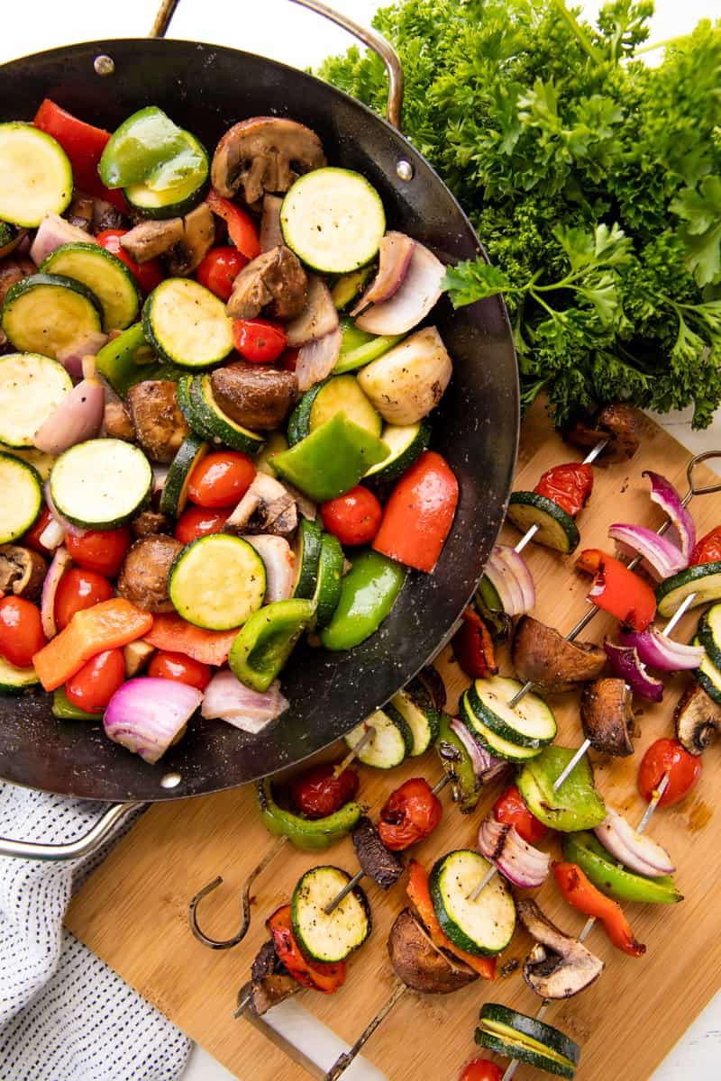 Fresh vegetables tossed with seasoning in a grill pan and grilled veggie kebabs on metal skewers on a cutting board