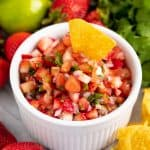 A tortilla chip is dipped into a bowl of strawberry salsa, surrounded by fresh strawberries, lemon, cilantro and tortilla chips