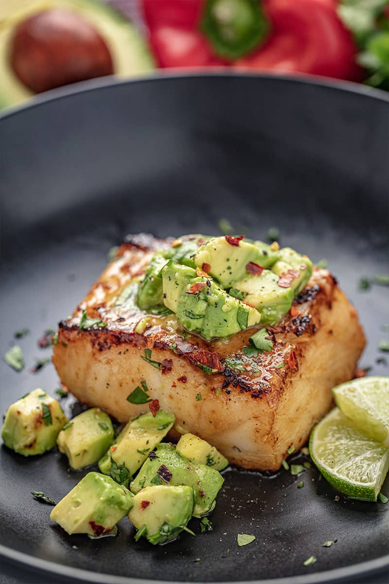 A closeup of Avocado Salsa Sea Bass in a skillet with avocado salsa and slices of lime