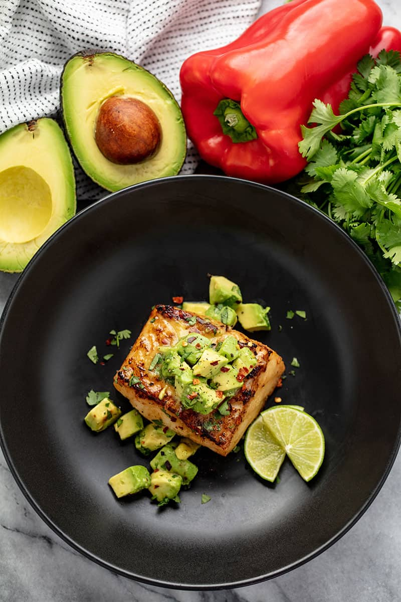 Avocado Salsa Sea Bass in a skillet with avocado salsa and slices of lime