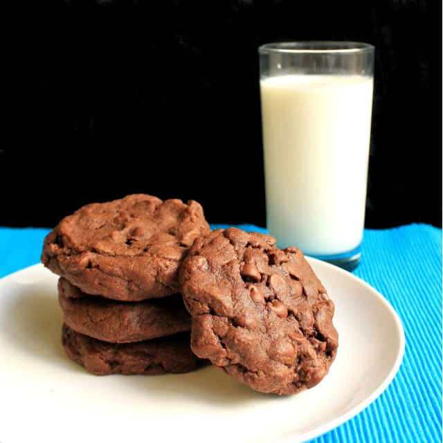 A stack of Chocolate Cookies on a white plate by a glass of milk