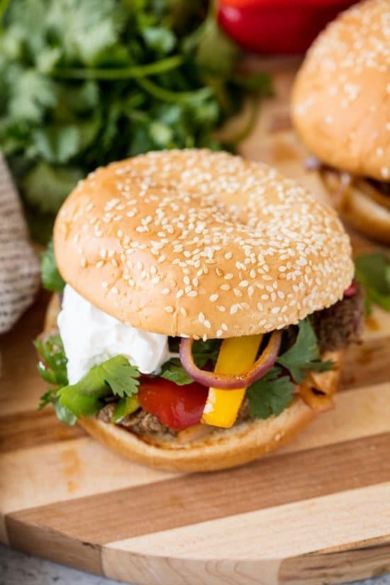 Fajita Burgers with grilled steak, bell pepper, red onion, cilantro and sour cream on a Sesame Bun