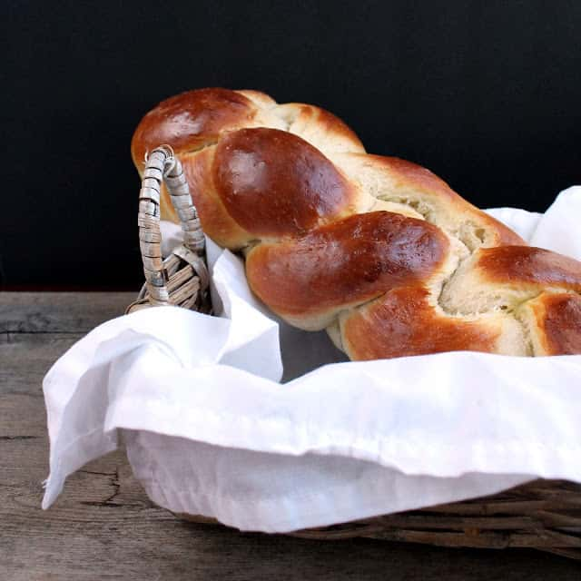 Challah bread in a basket covered in a white cloth.