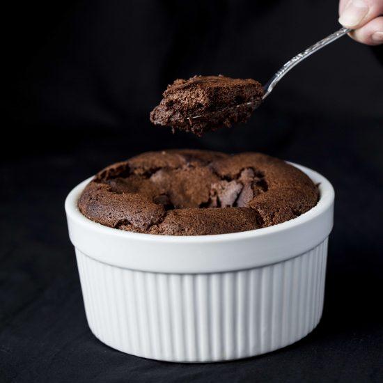 Spoon of chocolate souffle over a ramekin of chocolate souffle