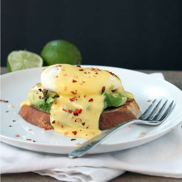 Eggs Benedict a la Avocado Toast on a white plate next to a fork.