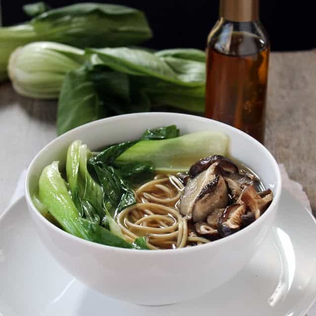 Ramen with mushrooms and green vegetables in it all in a white bowl.