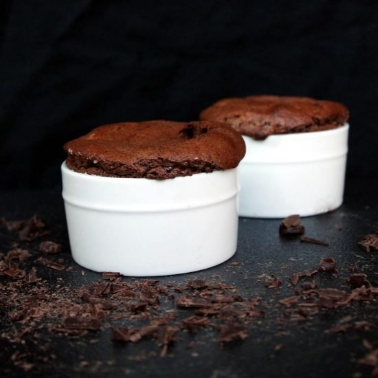 Two chocolate souffles in white ramekins with chocolate flakes around them