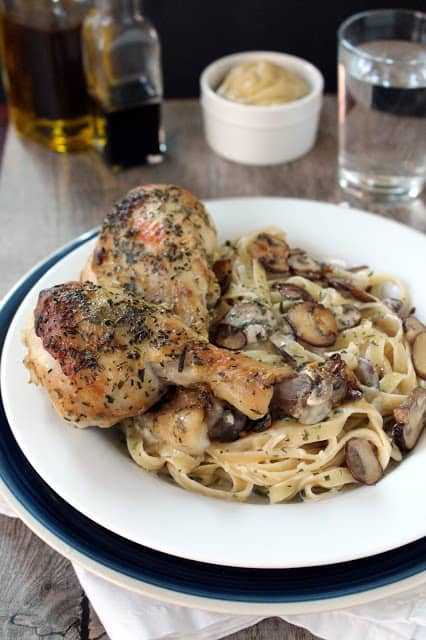 Tarragon Dijon roasted chicken with tarragon cream pasta  on a white plate with oil in the background