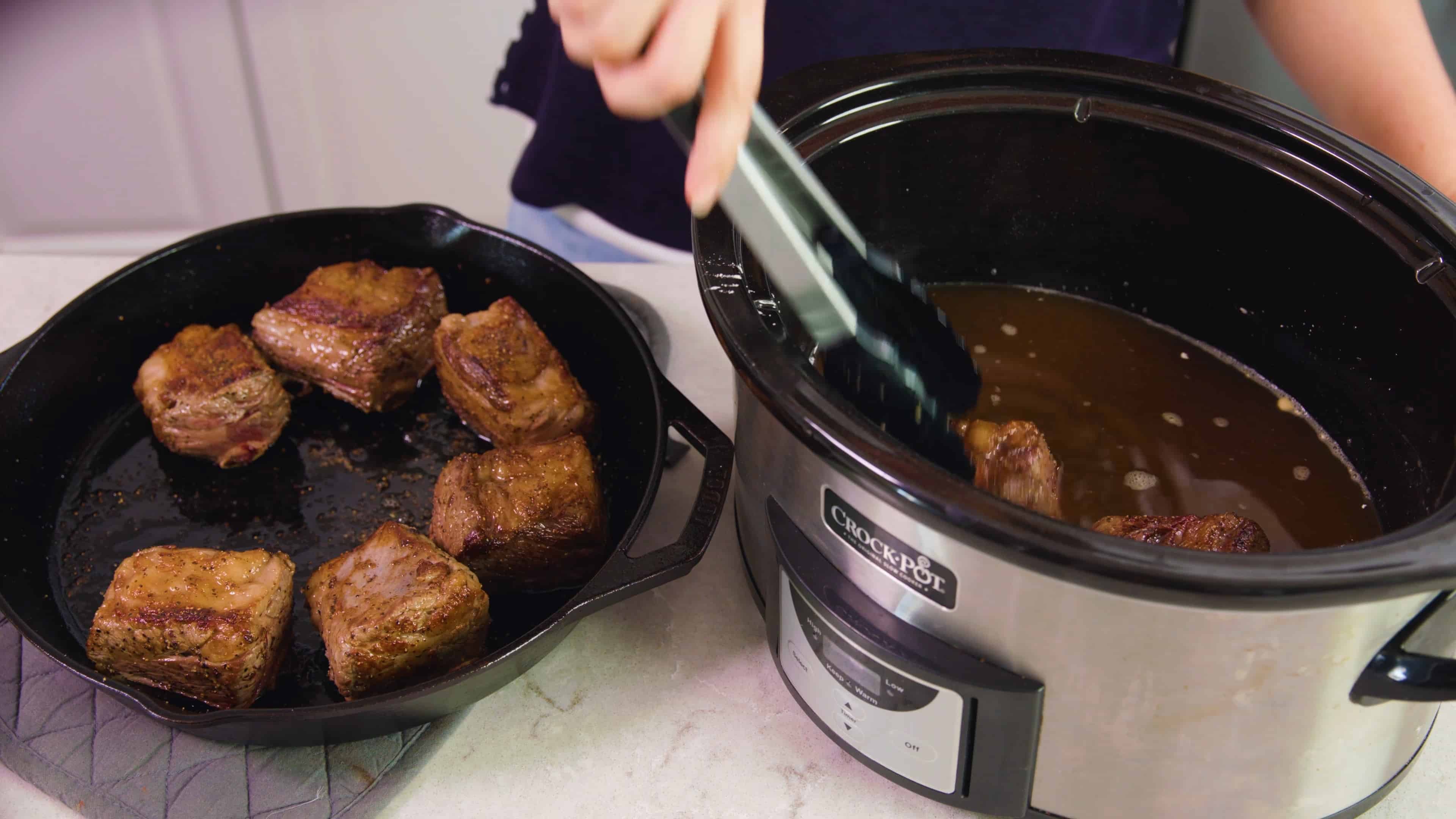 Seared beef short ribs being placed into the slow cooker.