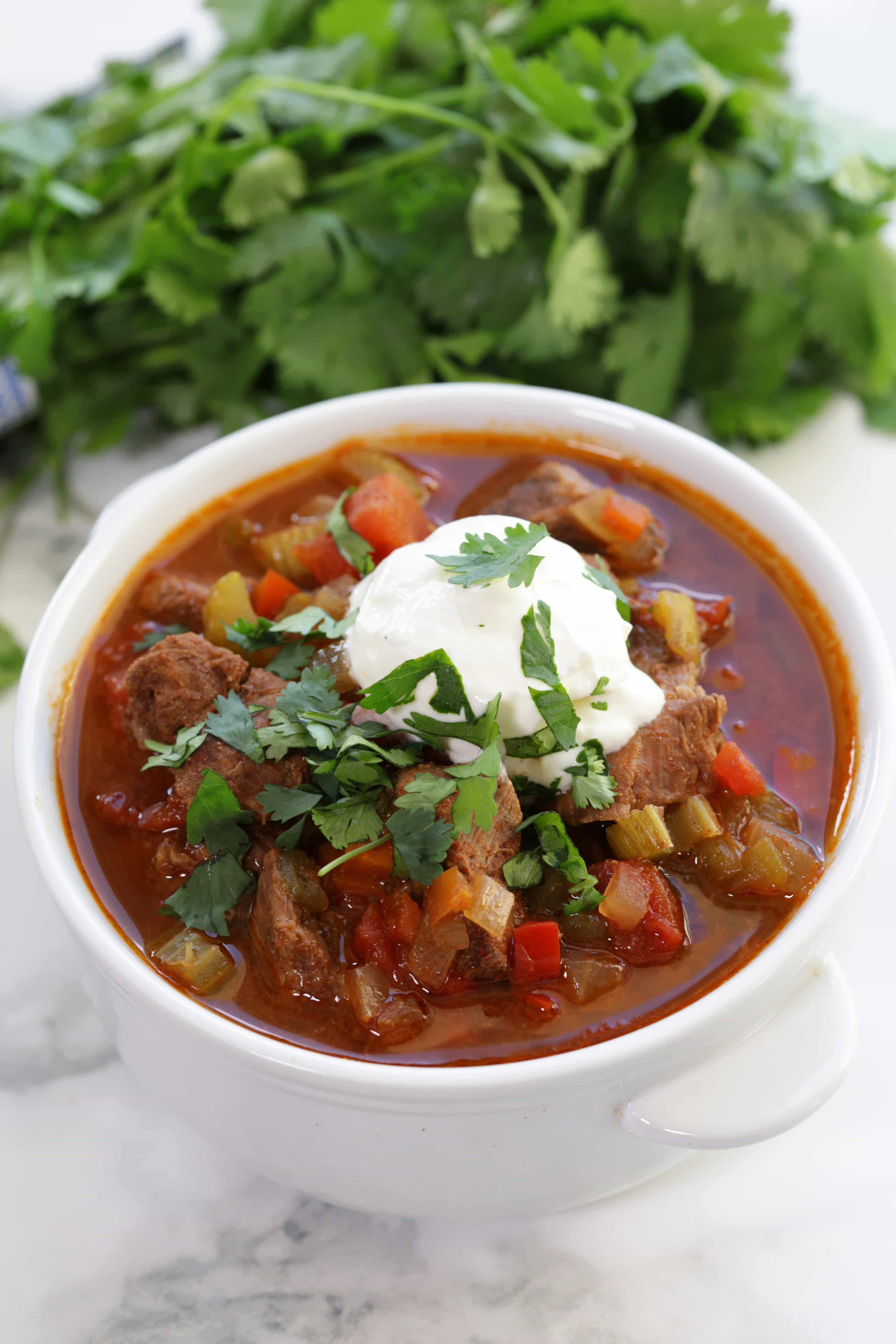 Slow Cooker Texas Beef Chili served in a bowl with a dollop of sour cream and garnished with fresh cilantro.