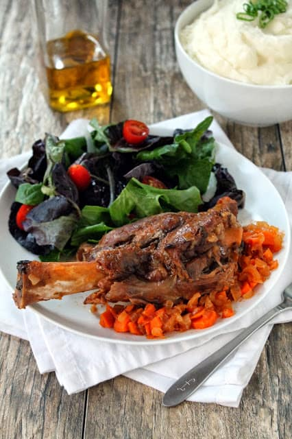 Above view of a Lamb shank on a white plate with slow cooker vegetables and a deep green salad.