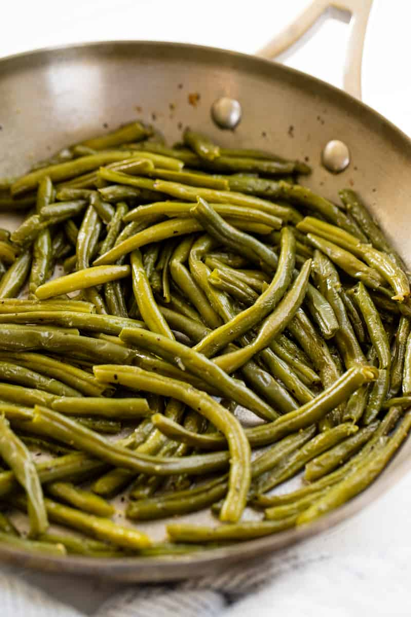 Cooked green beans in a stainless steel skillet