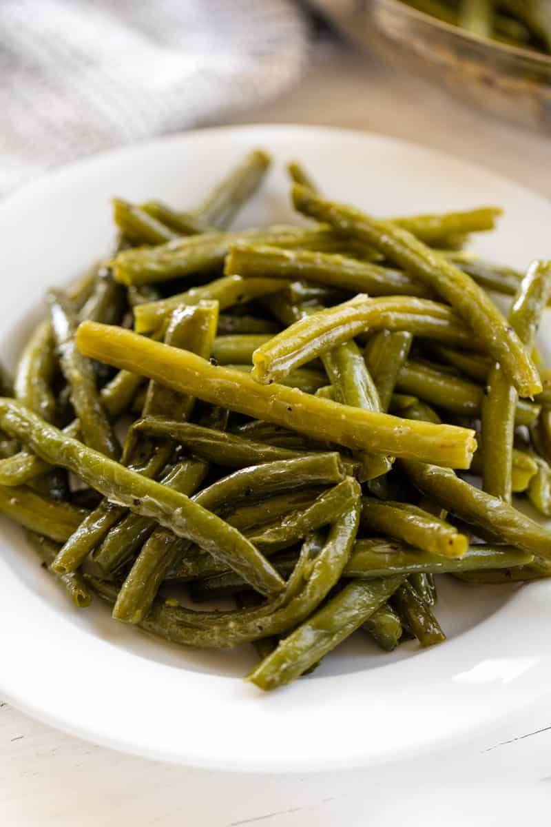 Cooked green beans on a white plate.