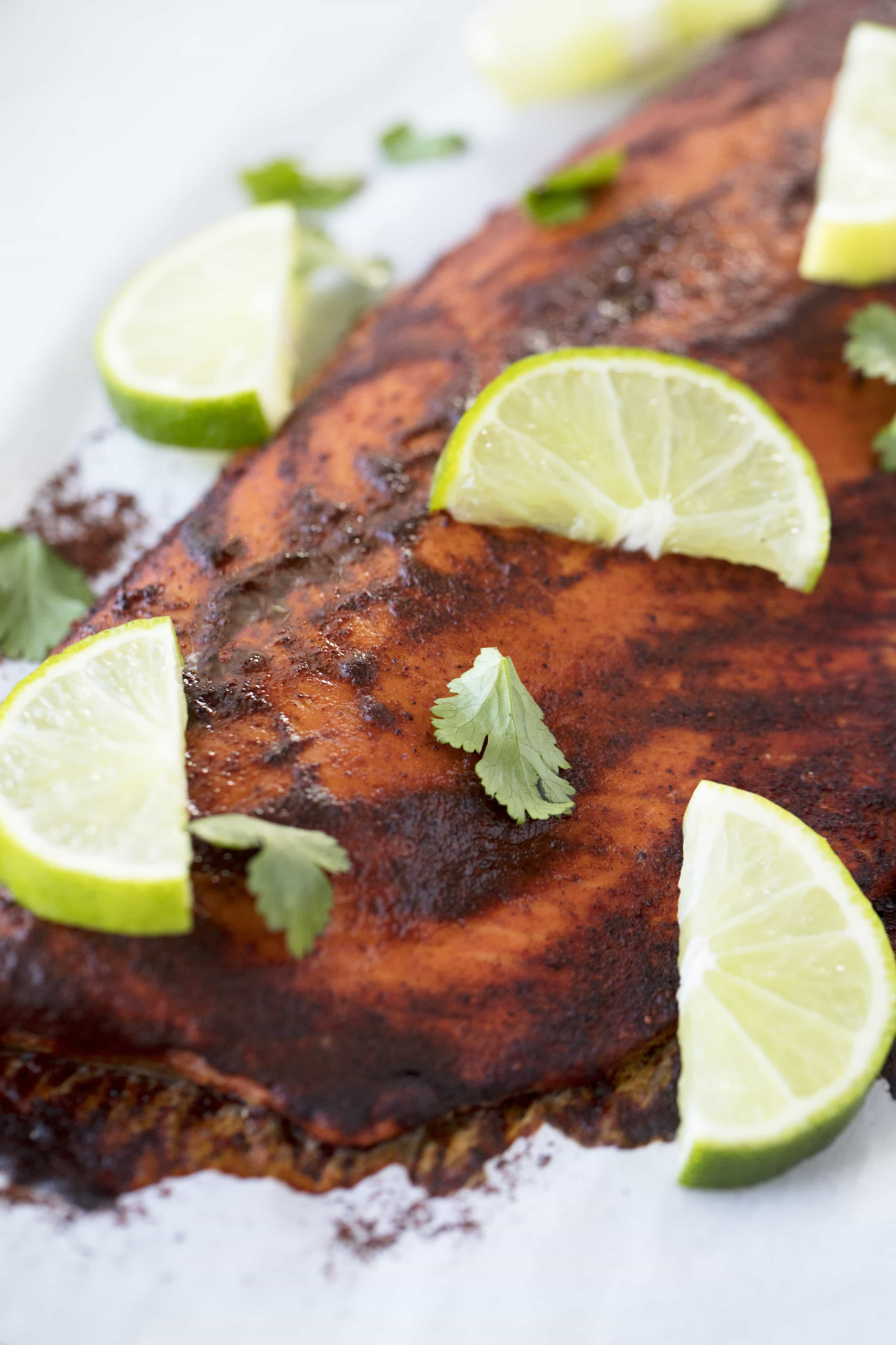 Baked Chili Lime Salmon with sliced limes on it.