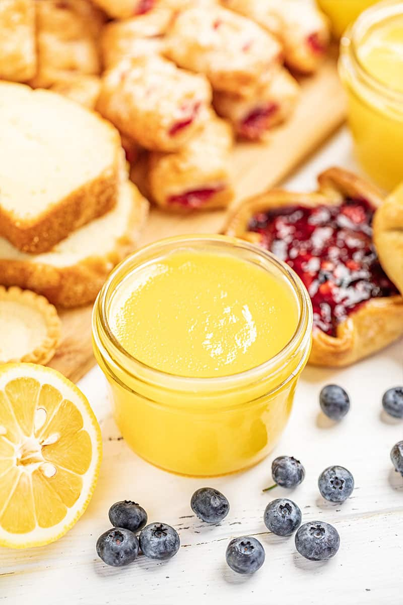 Lemon curd on a white countertop surrounded by desserts and fruit.