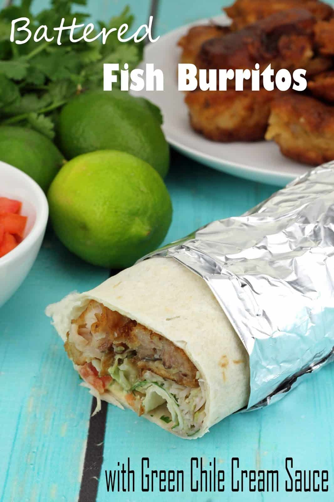 Battered Fish Burritos with Green Chile Sauce cut open to show the insides and wrapped in foil