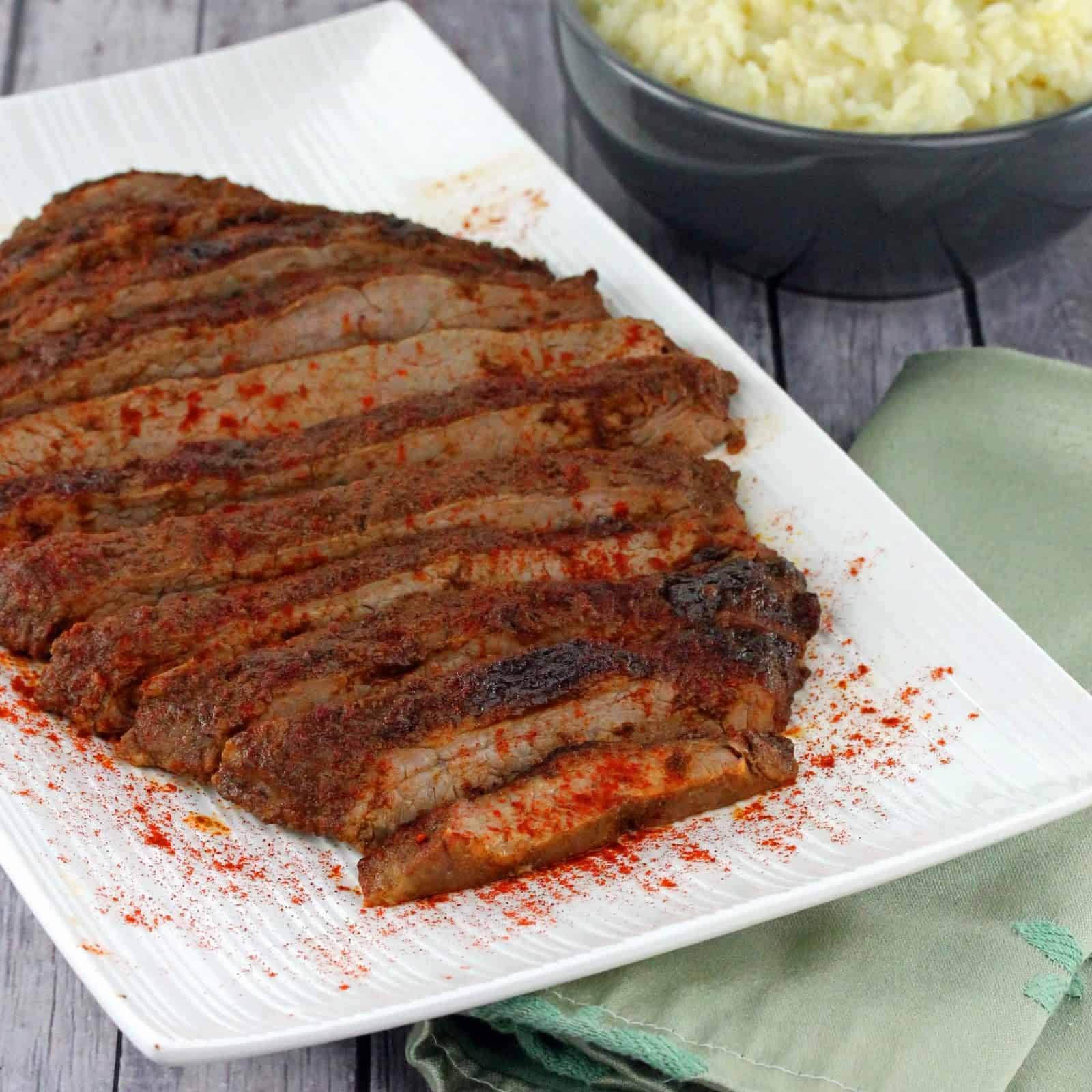 Oven Roasted Flank steak on a white serving plate.