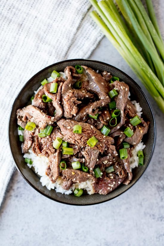 Korean beef bulgogi in a bowl on top of rice and topped with sesame seeds and green onions
