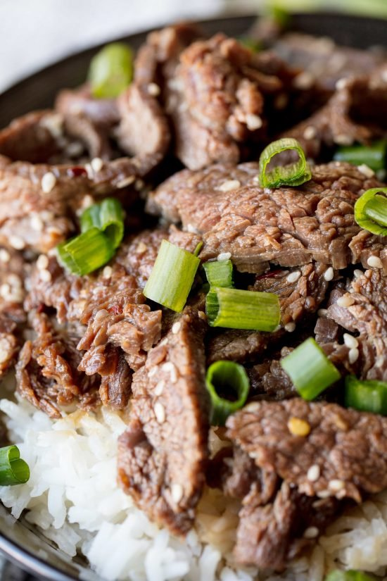 Detail of Korean Beef Bulgogi with thinly sliced beef, sesame seeds and chopped fresh green onion