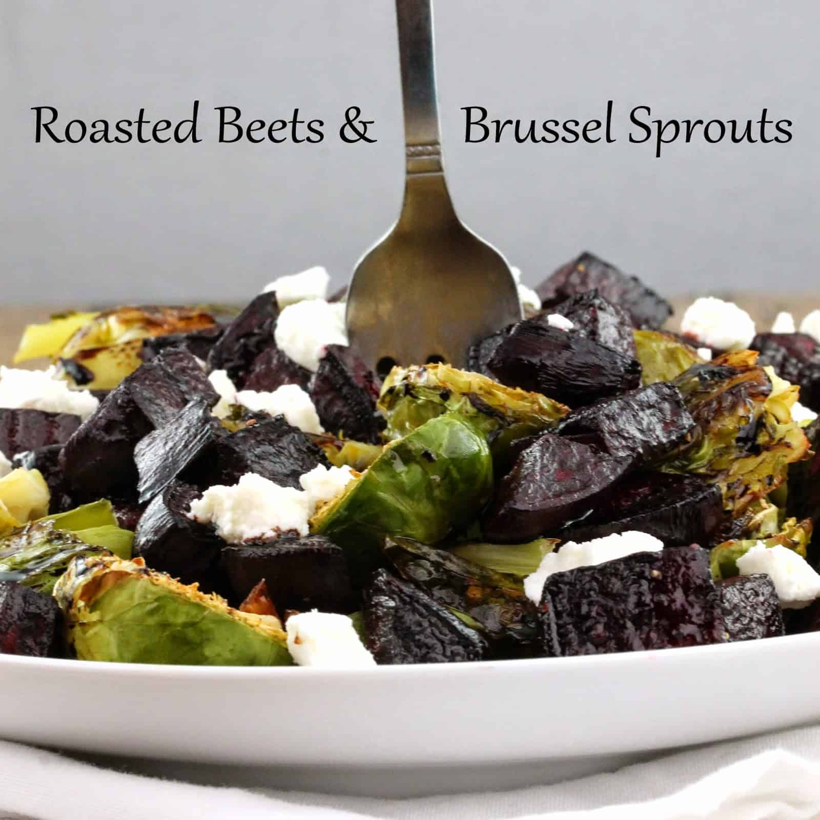 Beets and brussel sprouts topped with goast cheese in a white bowl with a fork in the middle of it.