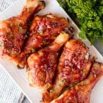 Honey Garlic Barbecue Chicken Drumsticks are finger-licking good! A homemade honey garlic barbecue sauce smothered on chicken drumsticks with a cooking hack that makes it incredibly easy!