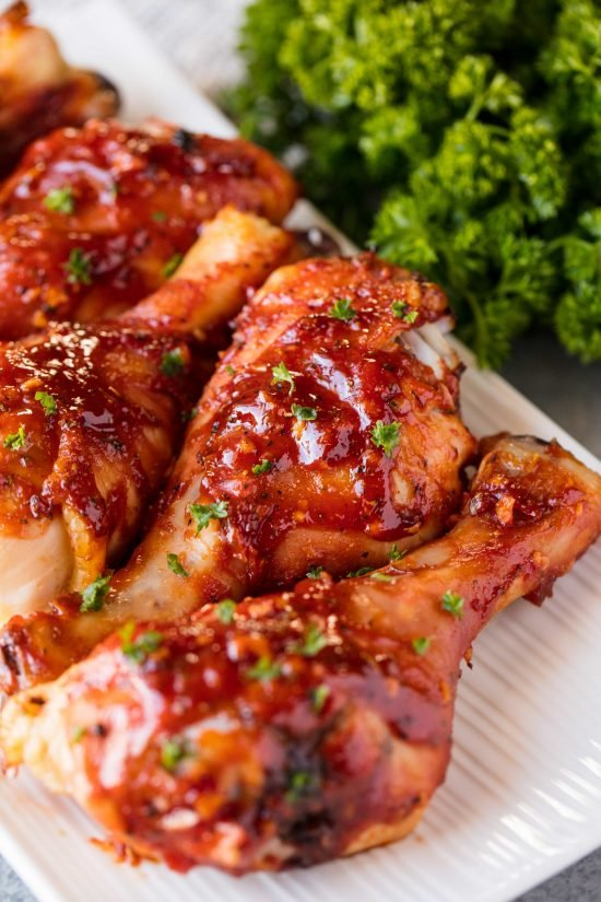 Honey garlic barbecue chicken drumsticks laid out on a white serving platter